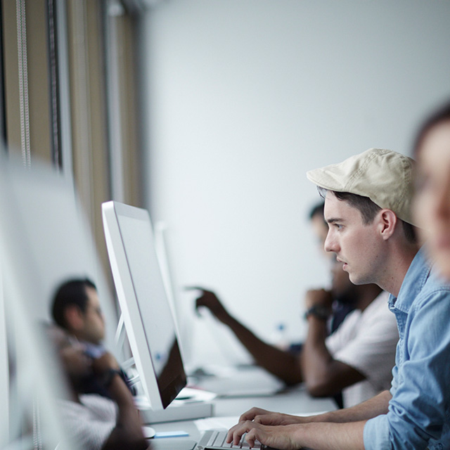 People sitting at a desk while looking at their computer monitors.