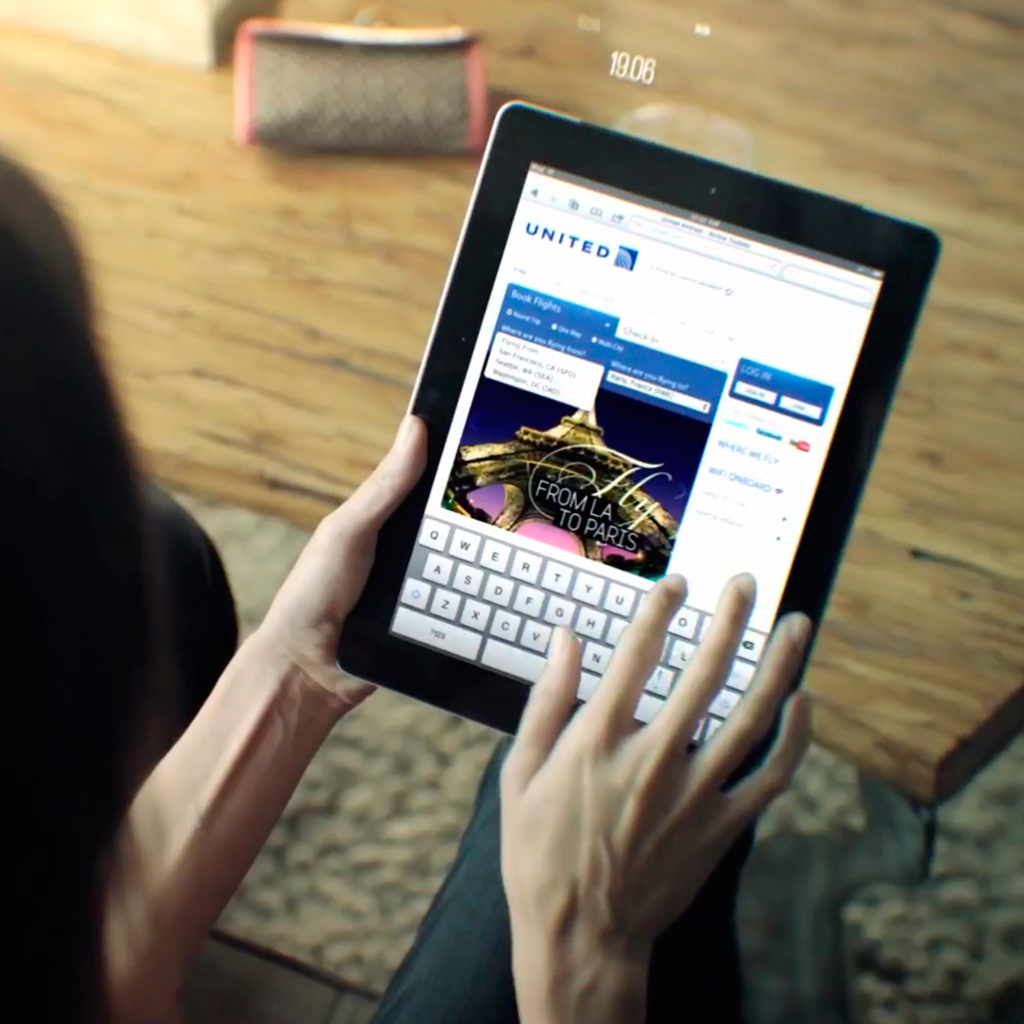 Woman holding a tablet navigating a website.
