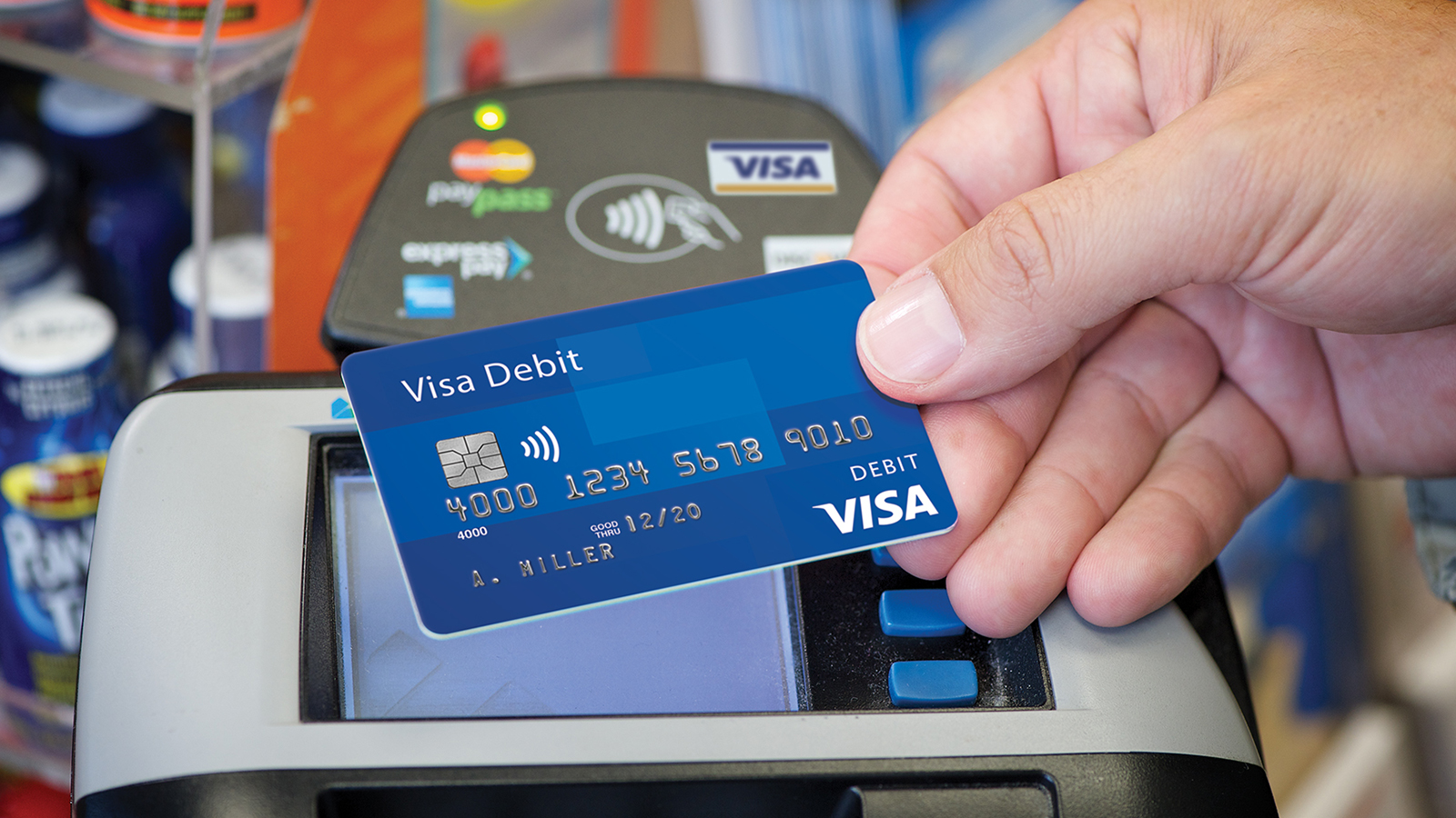 Person using a Visa payWave debit card at a payment terminal.