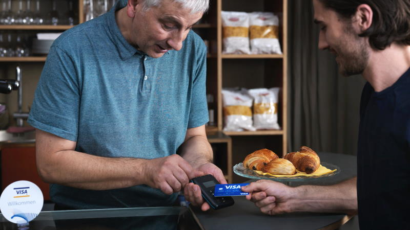 Man paying with contactless card in cafe